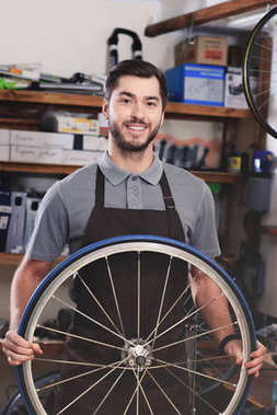handsome young worker in apron holding bicycle wheel and smiling at camera in workshop