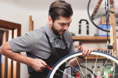 young male worker in apron fixing bicycle wheel in workshop