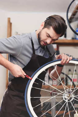 handsome young worker in apron fixing bicycle wheel in workshop