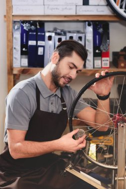 smiling young man in apron fixing bicycle wheel in workshop