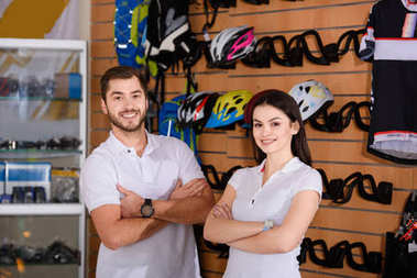 confident young workers standing with crossed arms and smiling at camera in bicycle shop