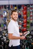 csinos, fiatal férfi gazdaság digitális tabletta, és mosolyogva kamera kerékpár szaküzlet
