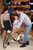 Fotografie Mutter Vater helfen kleinen Sohn Reiten neue Fahrrad im Bike-Shop betrachten