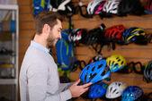 usměvavý mladý muž, který držel cyklistická přilba v prodejně kol