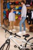 Fotografia vista ravvicinata del padre con il figlio in piedi dietro nel negozio di biciclette e biciclette nuove