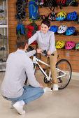 Fotografie Vater betrachtet man glücklich kleiner Sohn sitzen auf neues Fahrrad im Bike-shop