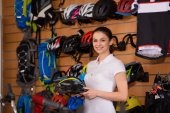 Photo young woman holding bicycle helmet and smiling at camera while working in bike shop