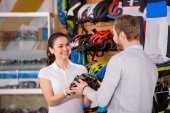 vevő és az eladó bicikli sisak gazdaság, és mosolyogva egymást a kerékpár üzlet