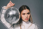 Fotografie portrait of young fashionable woman with disco ball in hands isolated on grey