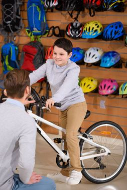 father looking at happy son riding new bicycle in bike shop