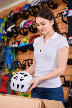 smiling young woman putting bicycle helmet in cardboard box while working in bike shop