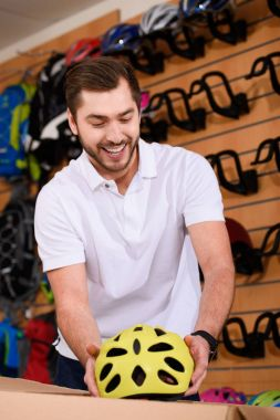 smiling young man taking bicycle helmet from cardboard box in bike shop