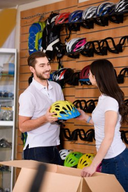 smiling young workers holding bicycle helmet and looking at each other while working together in bike shop