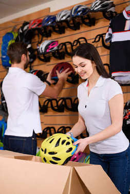 smiling young workers arranging bicycle helmets on shelves in bike shop