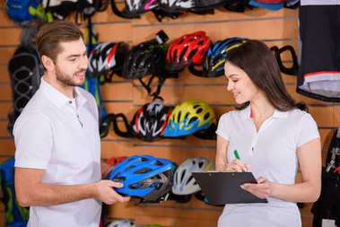 smiling young man and woman working together in bicycle shop