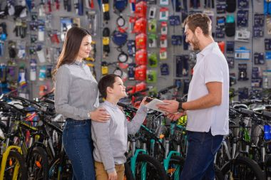 manager with digital tablet helping to choose bicycles to customers in bike shop