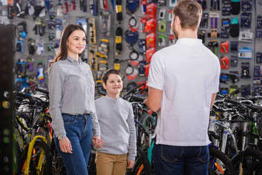 back view of seller looking at smiling mother and son in bike shop