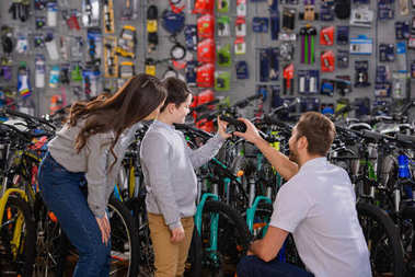 manager helping to choose bicycle to happy mother and son in bike shop