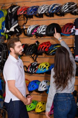 smiling young manager looking at woman choosing bike helmet in bicycle shop