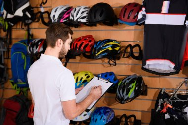 young man writing on clipboard while working in bicycle shop
