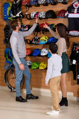 young parents with son choosing bicycle helmet in bike shop