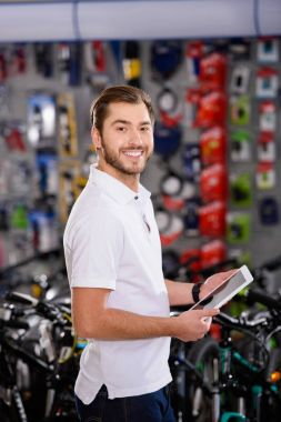 handsome young man holding digital tablet and smiling at camera in bicycle shop