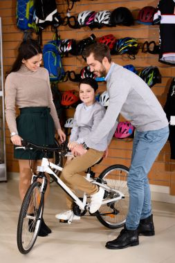 mother looking at father helping little son riding new bicycle in bike shop