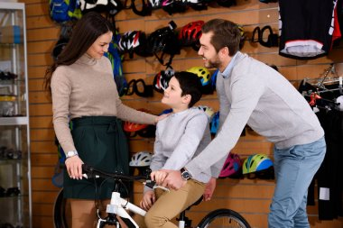 happy parents looking at smiling son sitting on bicycle in bike shop