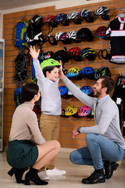 parents looking at happy son wearing bicycle helmet and raising hands in bike shop
