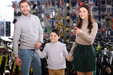 happy young family pointing with finger and looking away in bicycle shop