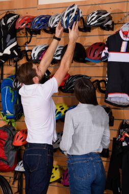 young manager helping to choose bicycle helmet to female customer in bike shop