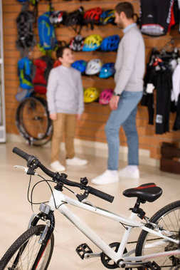 close-up view of new bicycle and father with son standing behind in bike shop