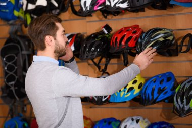 handsome young man looking at bicycle helmets in bike shop