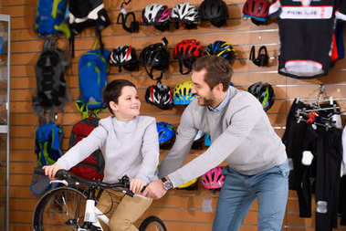 happy father helping cute smiling son riding new bicycle in bike shop