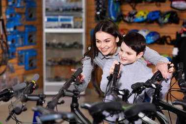 happy young mother with cute little son looking at bicycles  in bike shop