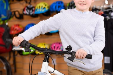 cropped shot of smiling little boy standing with bicycle in bike shop
