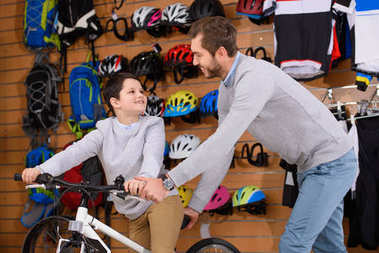 happy father and son smiling each other while choosing new bicycle in bike shop
