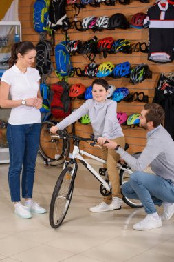 smiling father and young female seller looking at happy boy sitting on new bicycle in bike shop