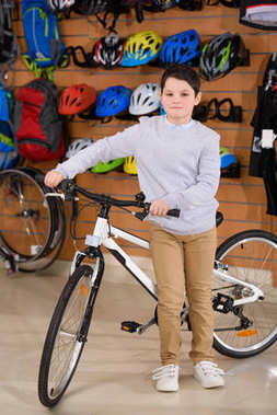 cute little boy standing with bicycle and looking at camera in bike shop