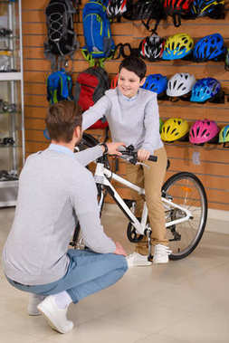 father looking at happy little son sitting on new bicycle in bike shop