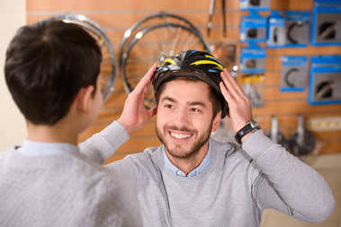 boy looking at happy father wearing bicycle helmet in bike shop