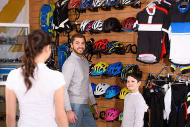 smiling father and son choosing bicycle helmets and looking at female seller in bike shop