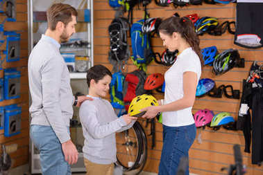 father, son and young female seller choosing bicycle helmet in bike shop