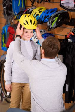 father looking at cute smiling son wearing helmet in bicycle shop