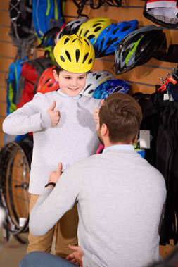 father looking at smiling son wearing bicycle helmet and showing thumbs up in bike shop