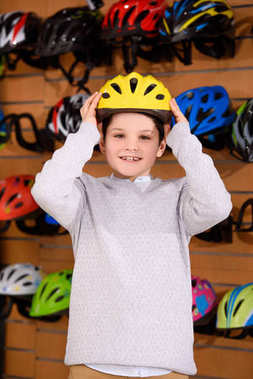 cute little boy putting on bicycle helmet and smiling at camera in bike shop