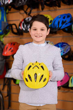 cute little boy holding helmet and smiling at camera in bicycle shop