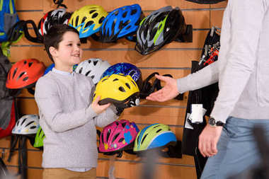 cropped shot of father and smiling son choosing helmet in bicycle shop