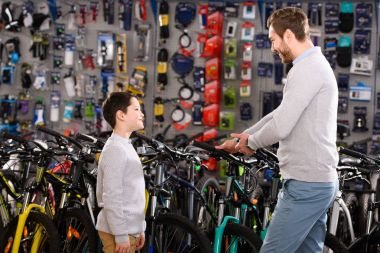 happy father and son looking at each other while choosing bicycles in bike shop