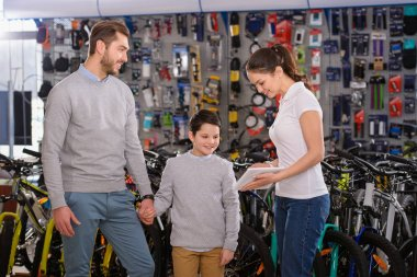 smiling young woman showing digital tablet to father and son choosing bicycles in bike shop